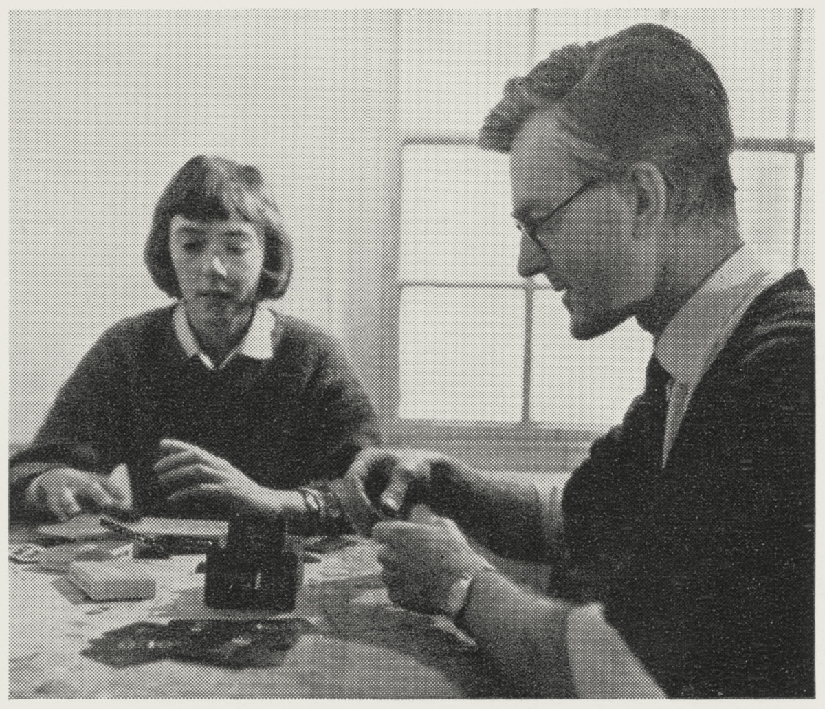 Jock Kinneir and Margaret Calvert playing cards at a table.