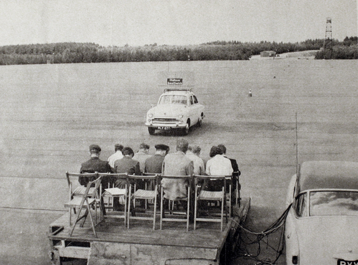 A group of a dozen cadets sat stationary on chairs on a raised platform observing a car driving towards them with a draft motorway-sign attached to its roof.
